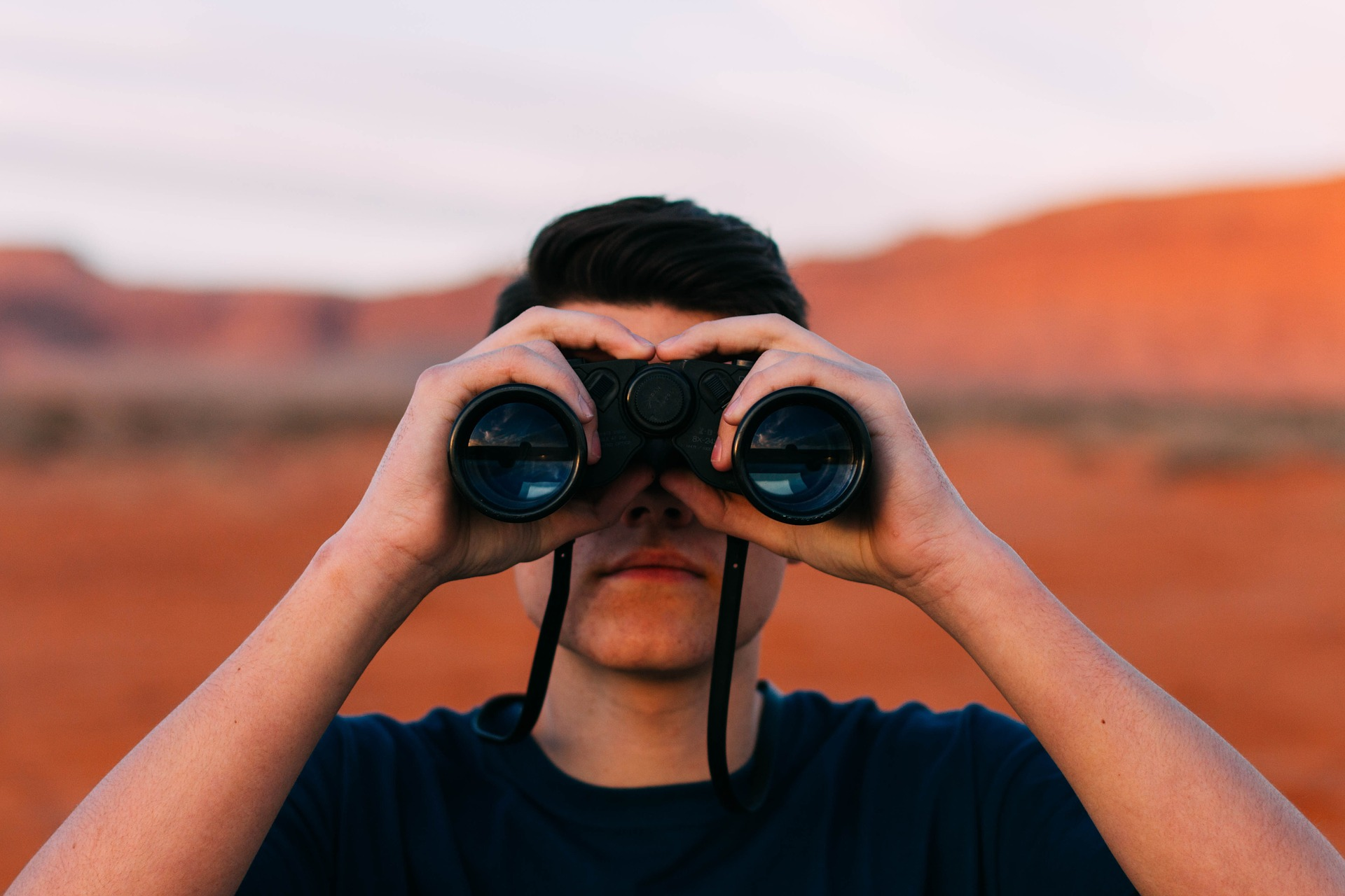uomo che guarda col binocolo verso il futuro
